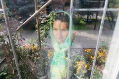 Reflexão de uma menina em um lenço em uma janela foto de stock royalty free