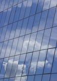 Reflexão do céu com as nuvens nas janelas de vidro da construção fotografia de stock