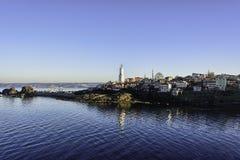 Reflexão do farol no mar sob céus azuis claros foto de stock royalty free