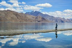 A reflexão do fotógrafo na água do lago Pangong imagens de stock