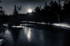 Reflexão do luar sobre a neve do rio do inverno em bancos imagem de stock