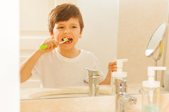 Reflexão do menino no espelho durante a escovadela de dente imagens de stock