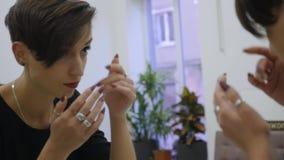 Reflexão do penteado curto do cliente fêmea no espelho Conceito da forma e da beleza filme