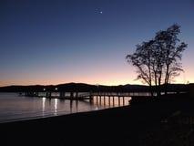 Reflexão do por do sol da beira do lago no crepúsculo Fotos de Stock Royalty Free