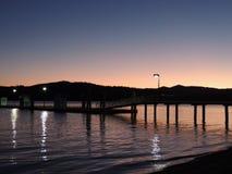 Reflexão do por do sol da beira do lago no crepúsculo Imagem de Stock Royalty Free