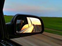 Reflexão do por do sol no espelho de rearview automotivo fotografia de stock