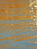 A reflexão do ` s do sol irradia na água Imagens de Stock