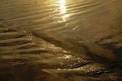Reflexão do sol da noite na areia molhada imagem de stock royalty free