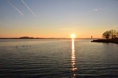 A reflexão do sol no por do sol foto de stock