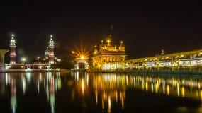 Reflexão do templo dourado na noite na superfície da água do lago próximo fotografia de stock