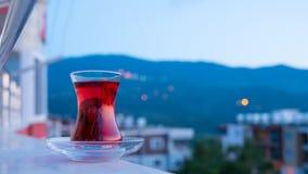 A reflexão e a luz do céu com o copo turco do chá durante o por do sol do dia à noite decorrem em Turquia, inclinação para baixo video estoque