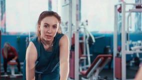 A reflexão na menina nova da aptidão do espelho executa um exercício com um peso filme