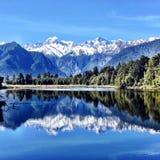 reflexão Neve-tampada da montanha no lago claro azul fotos de stock royalty free