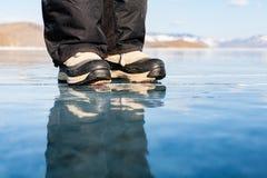 A reflexão no gelo transparente Pé humano nas sapatas no th Imagens de Stock Royalty Free