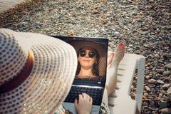 Reflexão no monitor do portátil de uma menina com vidros e de um chapéu novos, sorrindo, freelancer na costa foto de stock royalty free