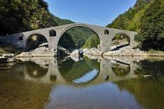 Reflexão surpreendente da ponte do diabo no rio de Arda e na montanha de Rhodopes, Bulgária imagem de stock