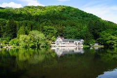 Reflexão verde natural abundante bonita da inclinação de montanha no lago fresco Kinrinko com construções durante a primavera imagens de stock royalty free
