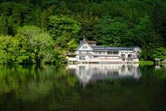 Reflexão verde natural abundante bonita da planta da montanha no lago fresco Kinrin com construções durante a primavera imagem de stock royalty free