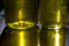 Reflexões amarelas através das garrafas de óleo Imagem de Stock Royalty Free