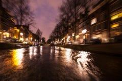 Reflexões da iluminação da noite nos canais de Amsterdão de barco movente do cruzeiro Foto abstrata borrada como o fundo Imagem de Stock Royalty Free