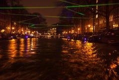 Reflexões da iluminação da noite nos canais de Amsterdão de barco movente do cruzeiro Foto abstrata borrada como o fundo Fotos de Stock Royalty Free