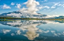 Reflexões da montanha em um lago glacial azul vívido no Alaskan imagens de stock
