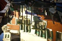 Reflexões dos barcos e de construções coloridas em Burano Itália Fotos de Stock Royalty Free