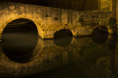 Reflex arcs. The bridge that leads to the fortress new to Livorno is reflected in ditches Royalty Free Stock Images
