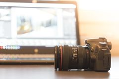 Reflex camera with professional telephoto lens on a table, laptop in the blurry background. Professional camera with telephoto lens on a table, laptop in the stock image