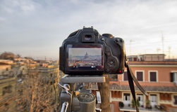 Reflex camera on tripod. DSLR Camera On Tripod Shooting roofs of Rome Royalty Free Stock Photography