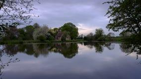Reflex?es da igreja de St Leonard em Hartley Mauditt Pond, penas sul parque nacional, Reino Unido fotografia de stock