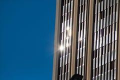 Reflex?es urbanas Os raios de sol refletiram no vidro de uma construção com fundo azul imagens de stock