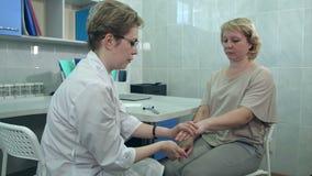 Reflex för neurologprovningsknä på en kvinnlig patient som använder en hammare arkivfilmer
