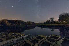Reflex?o das estrelas e das ?rvores no lago na noite Porto com barcos fotografia de stock