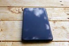 Reflex?o do c?u azul com as nuvens brancas na tela do smartphone em um fundo de madeira no borr?o imagem de stock