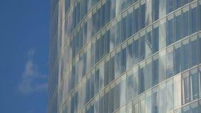 Reflexión brillante del cielo azul en vidrios de la ventana de edificio multi-storeyed moderno almacen de metraje de vídeo