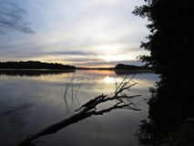 Reflexión caida del árbol en agua durante puesta del sol sobre el lago hermoso con el cielo nublado en fondo Foto de archivo libre de regalías
