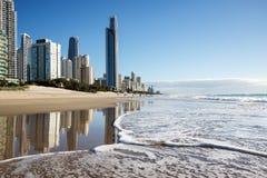 Reflexión de apartamentos en el océano en la playa Personas que practica surf paraíso, Gold Coast imagen de archivo