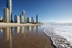 Reflexión de apartamentos en el océano en la playa Personas que practica surf paraíso, Gold Coast foto de archivo