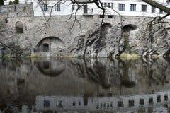 Reflexión de arcos, de ventanas y del acantilado en un río Fotos de archivo