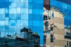 Reflexión de edificios antiguos en la fachada de cristal de un edificio moderno foto de archivo