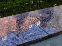 Reflexión de edificios en una losa mojada del granito Fotos de archivo