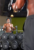 Reflexión de espejo de dos hombres que ejercitan en gimnasio Foto de archivo libre de regalías