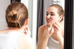 Reflexión de espejo de la muchacha con el acné que exprime sus espinillas Imagen de archivo libre de regalías