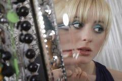 Reflexión de espejo de la muchacha que aplica el lápiz labial Imagen de archivo libre de regalías