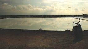 Reflexión de espejo del cielo y de las nubes en agua con la silueta de la moto del vintage - granja Tailandia de la sal del mar Foto de archivo