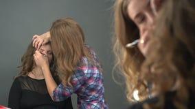 Reflexión de espejo del cliente femenino joven que mira en el espejo mientras que artista de maquillaje que trabaja en sus cejas almacen de video