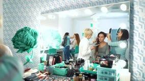 Reflexión de espejo de mujeres en el salón beaty que consigue maquillaje y corte de pelo almacen de metraje de vídeo