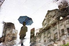 Reflexión de la ciudad en un charco Fotografía de archivo