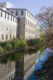 Reflexión de la fábrica a lo largo del río Imagen de archivo libre de regalías